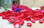 A girl busy in making earthen lamps ahead of Diwali in Jammu outskirts