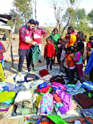 Volunteers of People's Hut Foundation distribute warm clothes in slums